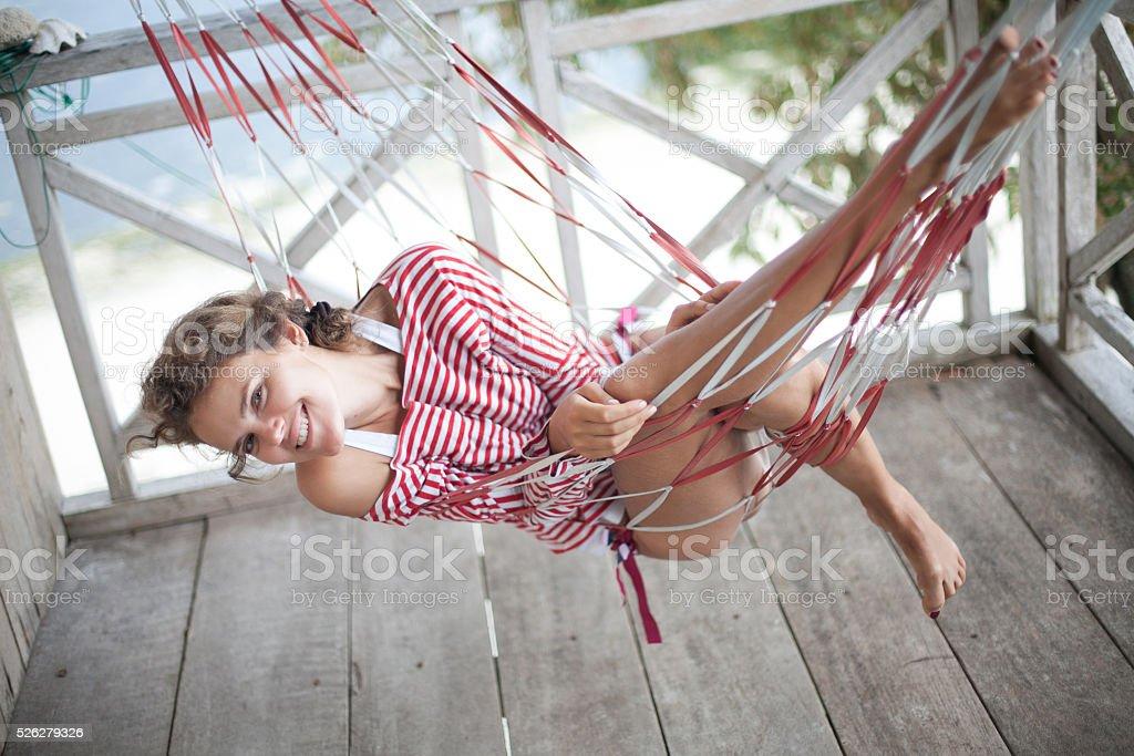 Фото молодая девушка расслабляющий на пляже в гамаке. Улыбающаяся женщина стоковое фото