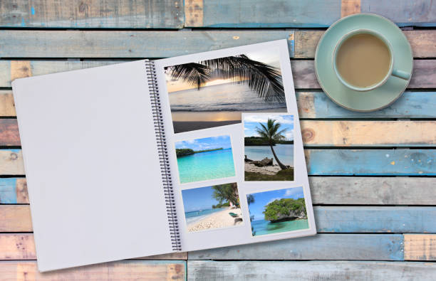 Photobook Album with Travel Photo on Wooden Floor Table with Coffee or Tea in Cup - foto stock