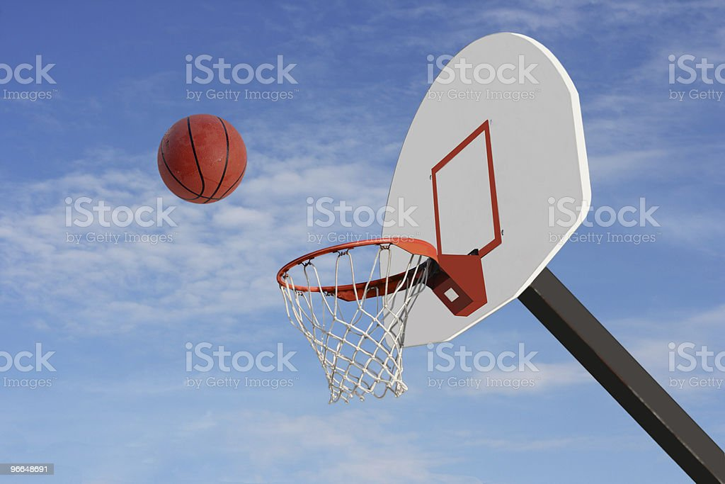 Photograph of a basketball going into a hoop outside royalty-free stock photo