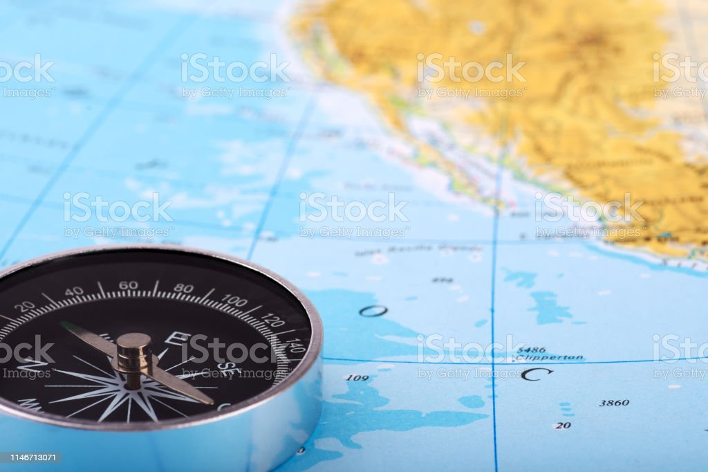 Photograph of a compass and a map of the atlas, with the ocean or the...
