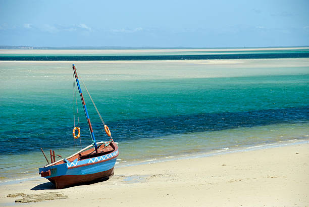 Photograph of a dhow sitting on the shoreline of an ocean stock photo