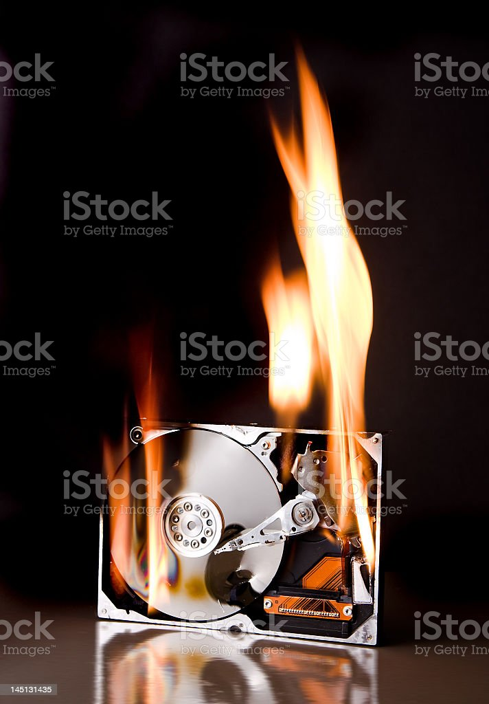 Photograph of a hard disk on fire with orange flames stock photo