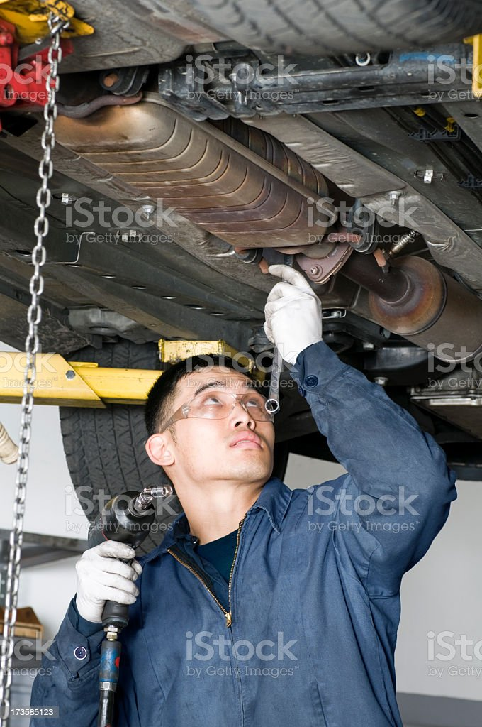 A photograph of a mechanic working under a car royalty-free stock photo