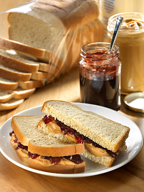 A photograph of a peanut butter and jelly sandwich Peanut Butter and Jam sandwich on whole grain white bread with peanut butter jar and jam jar in background with loaf of bread and bottle of milk. burwellphotography stock pictures, royalty-free photos & images