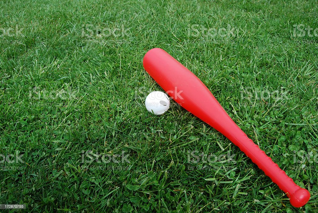 Photograph of a red bat and white ball lying on green grass stock photo