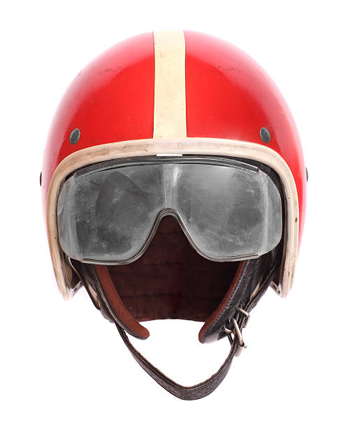 A photograph of a red motorcycle helmet and goggles stock photo