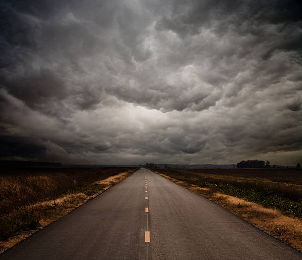 photograph of a straight road on a cloudy day - storm stock photos and pictures