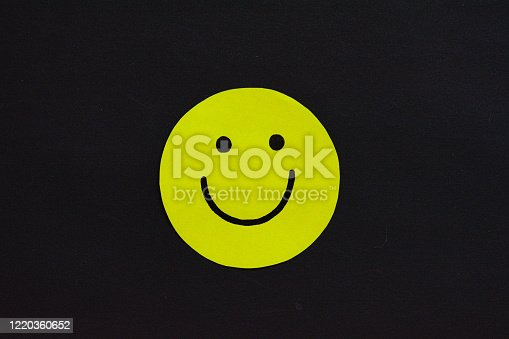 istock Photograph of a Yellow Circle with a Smiling Face Drawn on It on a Black Background. For business, personal, wellbeing 1220360652