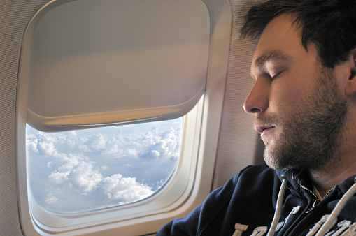 Young man sleeping on aircraft next by the window.