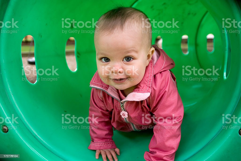 A photograph of a young toddler crawling through a tunnel royalty-free stock photo