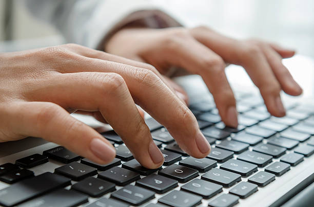 Photograph of hands working on data entry with keyboard stock photo