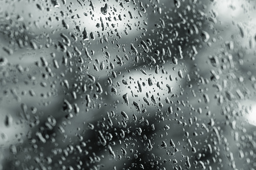 Photograph of the window of a car with raindrops.