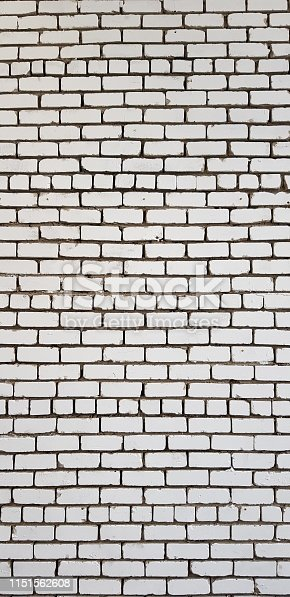 A photograph taken with a mobile phone camera is a vertical image of a wall made of horizontal rows of carelessly laid white brick. Variant of vintage abstract background.