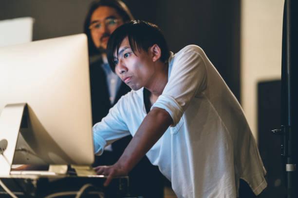 写真家、コンピューターで彼のモデル作って写真 - スタジオ 日本人 ストックフォトと画像