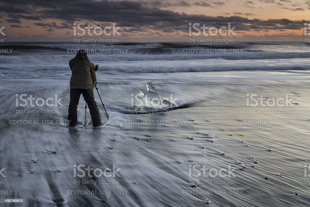 Photographer and iceberg on beach at sunset, Jokulsarlon, Icelan royalty-free stock photo