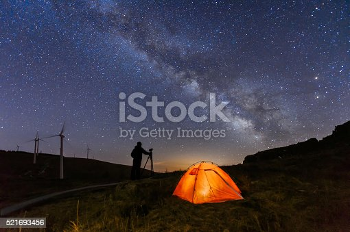 A Photographer is standing on the top of the hill next to the Milky Way galaxy with his hands on the tripod.