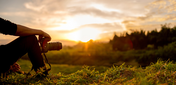 Nature photographer , Photographer are sitting look the sunset