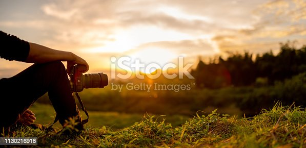 istock Photographer are sitting look the sunset 1130216918