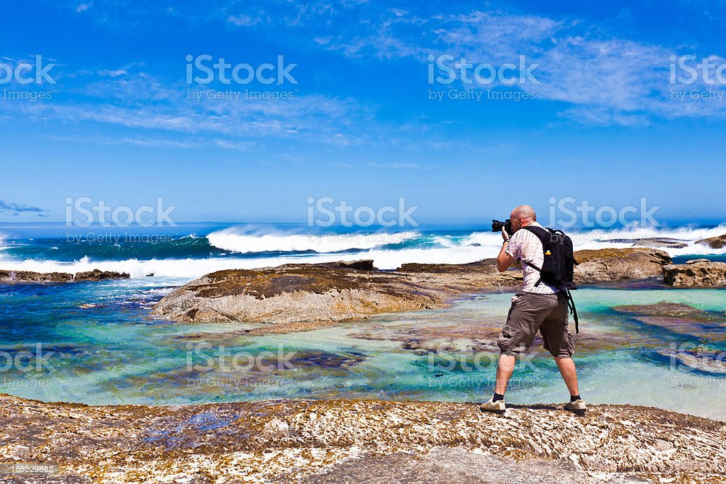 Photographer at coastline A photographer taking picture towards coastaline. Adult Stock Photo