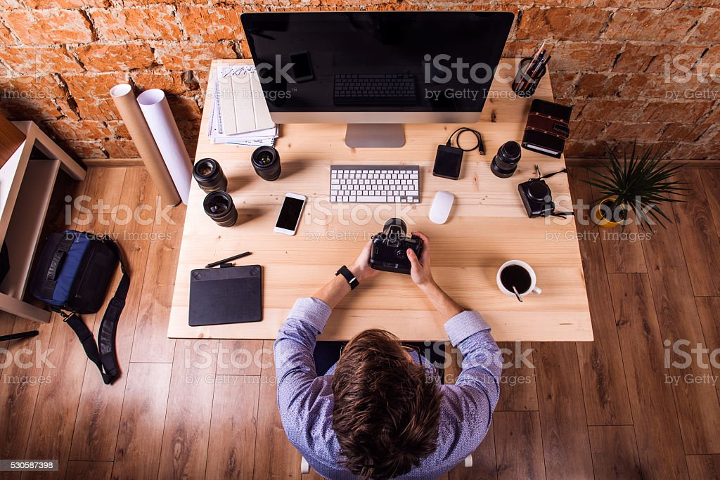 Photographer at the desk, office gadgets and object lens stock photo