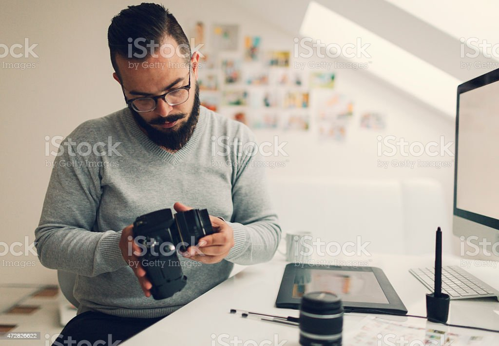 Photographer Changing Lens On His Digital Camera. stock photo