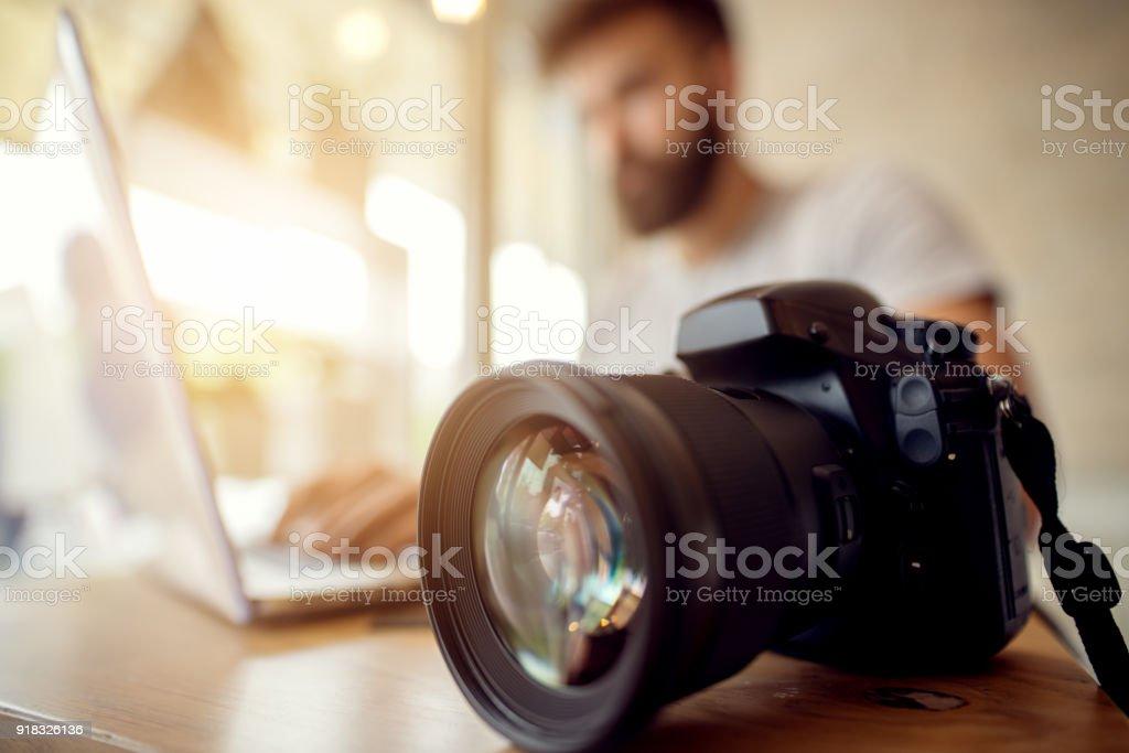 Photographer checking his files, off loading on laptop. Office worker journalist. stock photo