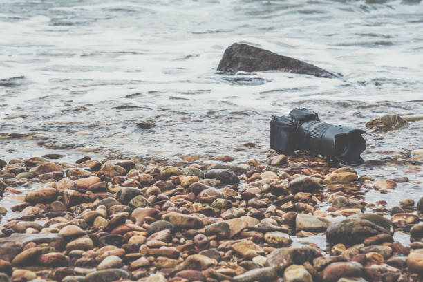 Photographer demo waterproof for DSLR camera and tele lens by wet from water sea wave at beach when travel and test using in the extreme environment stock photo