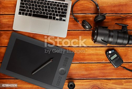 Photographer gear on wooden desk view from top. Photographer workspace view from top