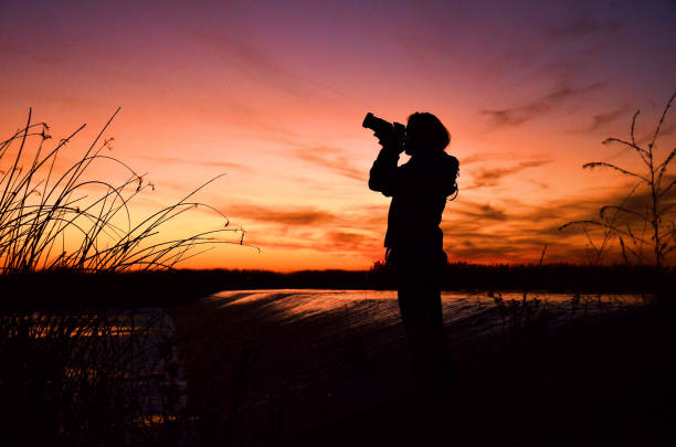 Photographer girl photographing sun with dslr stock photo