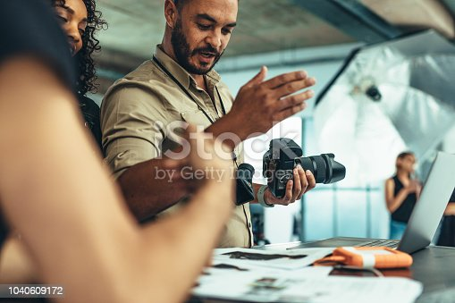 Photographer holding a digital camera doing a review of the photo shoot. Photographer discussing ideas with his team during photo shoot.