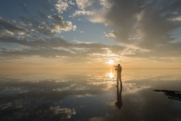 photographer  having fun walking on salt lake at sunset - opportunity stock photos and pictures