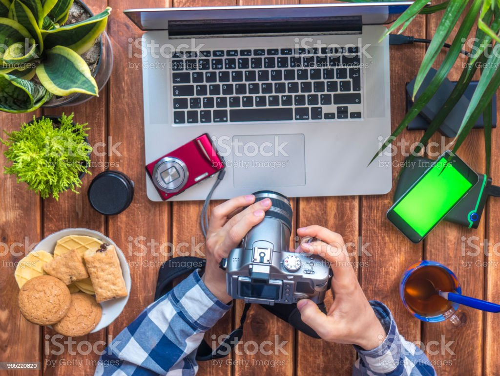 photographer holding camera at his working place with laptop royalty-free stock photo
