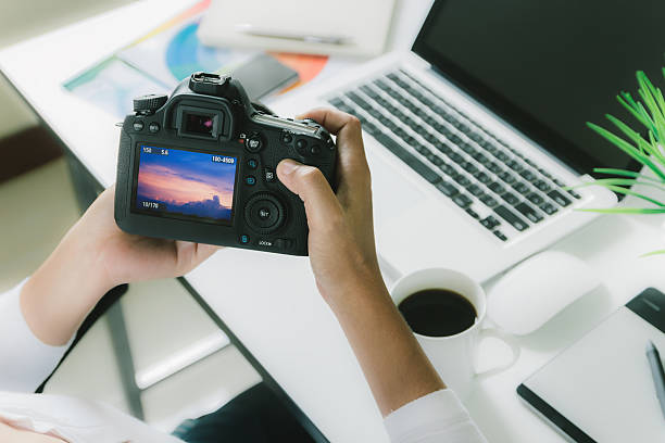 photographer holding camera checking photo on her desk workspace stock photo