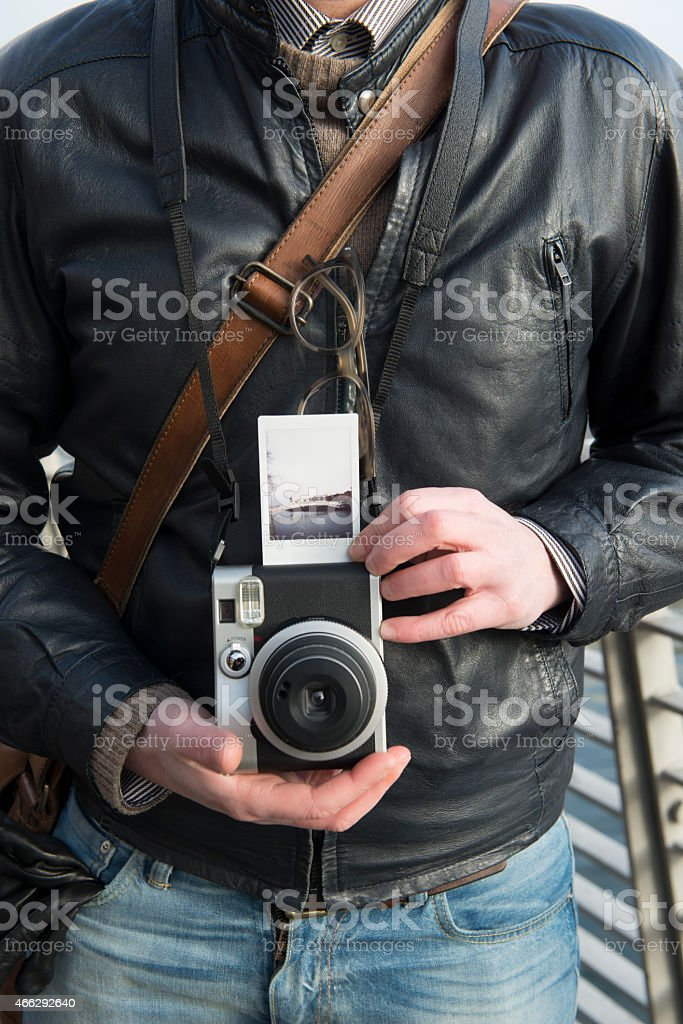 Photographer holding up an instant image of a bridge royalty-free stock photo