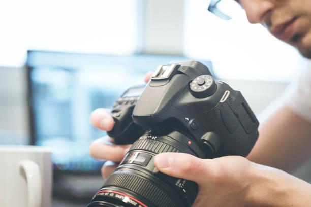 fotograaf heeft een reflex camera met telelens in zijn hand. tafel en laptop in de wazige achtergrond - spiegelreflexcamera stockfoto's en -beelden