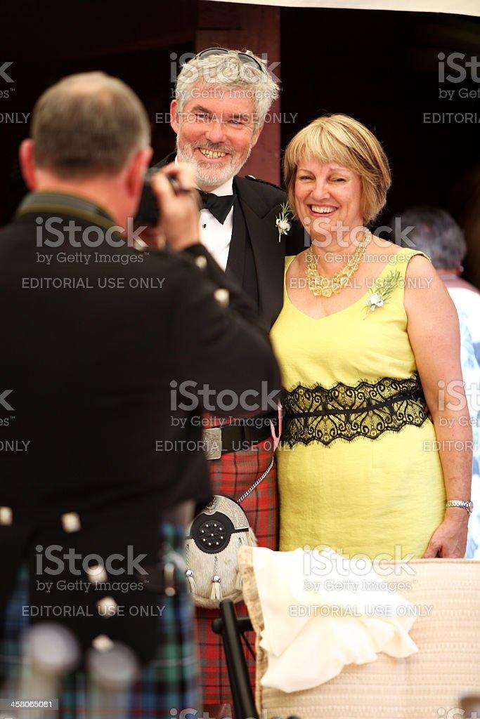 Photographer in Scottish kilt taking a picture of senior couple royalty-free stock photo