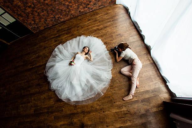 fotograf nimmt bilder die braut im der studio suite - hochzeitsbilder stock-fotos und bilder