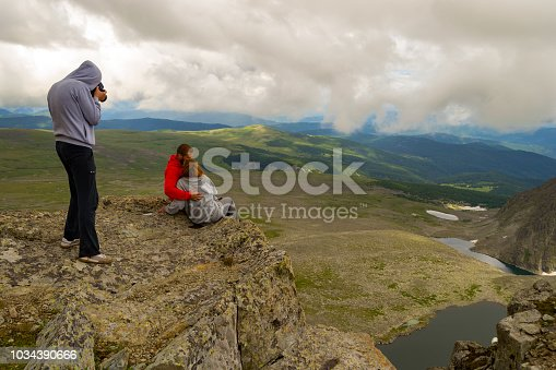istock A photographer makes a photo of a loving couple is standing on the Altai mountains kissing against the background of a valley bathed in sunlight, lakes with glaciers, rocks with snow and white clouds. 1034390666