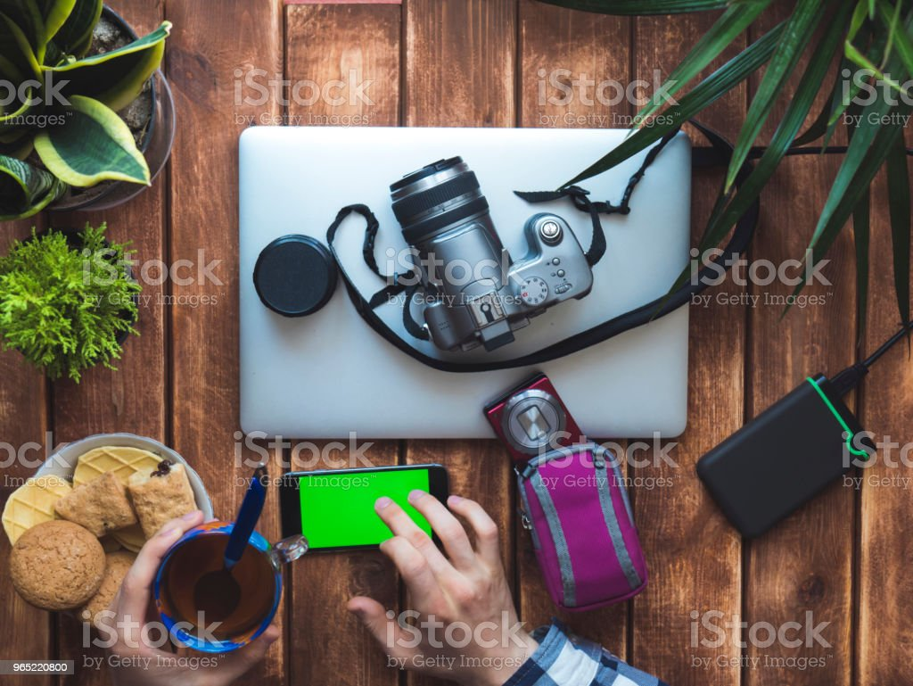 photographer making a break with cup of tea and mobile phone royalty-free stock photo