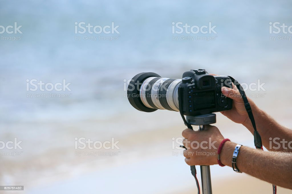 Photographer making a photo on the sea stock photo