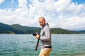 Photographer man in hoodie walking around lake with DSLR camera and shooting nature, half body portrait, landscape photography concept