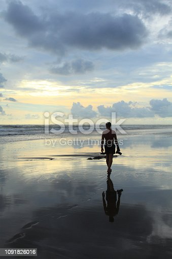 photographer with a camera walks along on the beach during an outflow