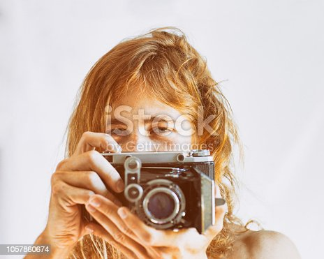 Portrait of photographer holding a classic film camera taking photo.