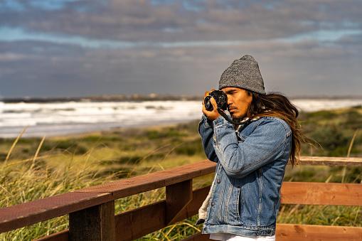 Photographer relaxes near grassy meadow above the beach