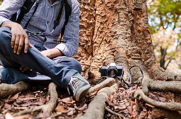 Photographer resting under a big tree with  Film camera stock photo