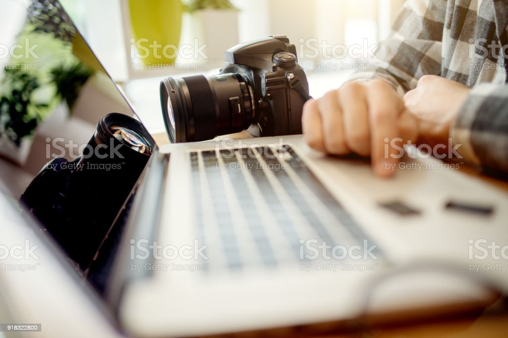 Photographer retouching photos on his computer. Work in progress after a successful photo shooting. stock photo