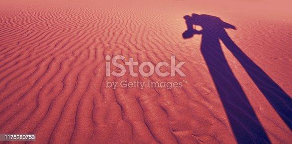Photographer shadow in sand dunes beach desert wavy texture coral filtered