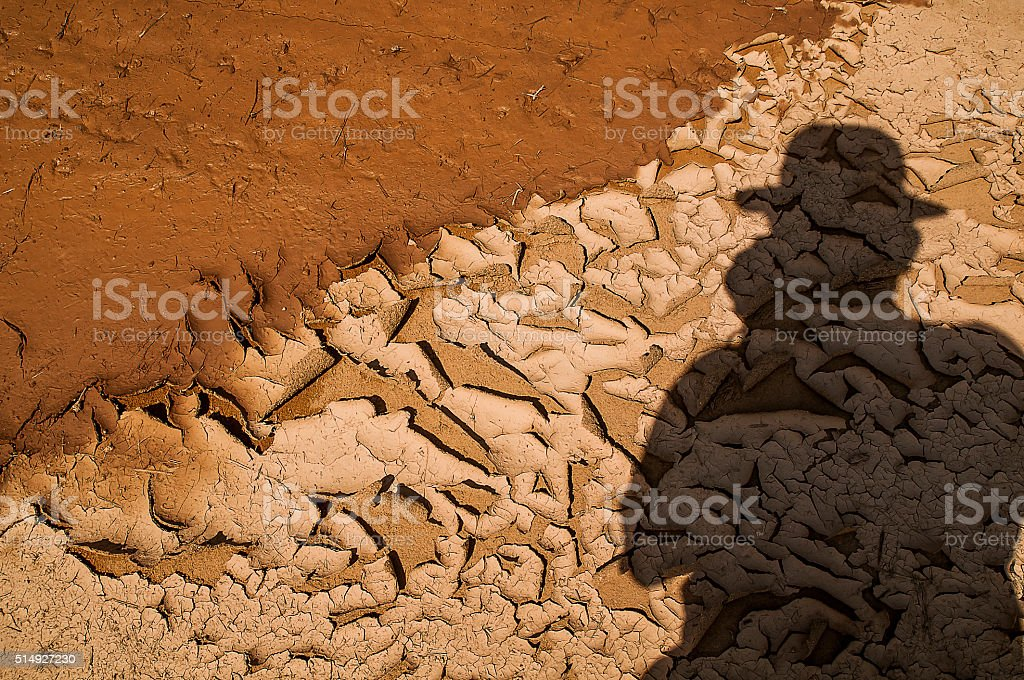 Photographer shadow on the dry mud , Thailand stock photo