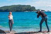 Photographer shooting his model, young beautiful caucasian woman.
