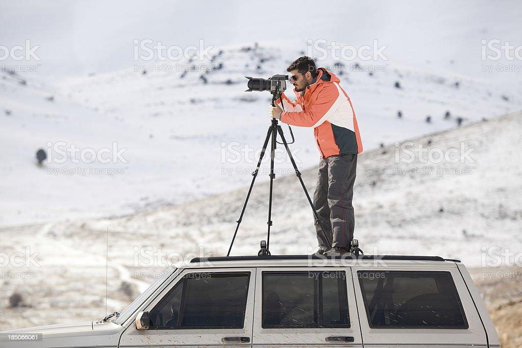 Photographer shooting on top of vehicle stock photo